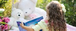 child reading book in garden