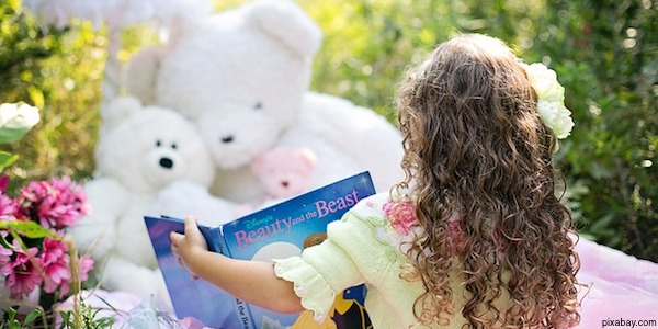 child reading book in garden